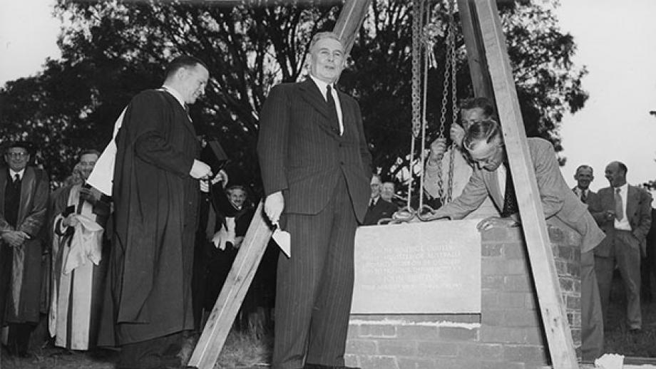 Ben Chifley, Prime Minister of Australia, accompanied by ANU architect Professor Brian Lewis, lays the foundation stone of the John Curtin School of Medical Research (now the Florey Building) October 1949