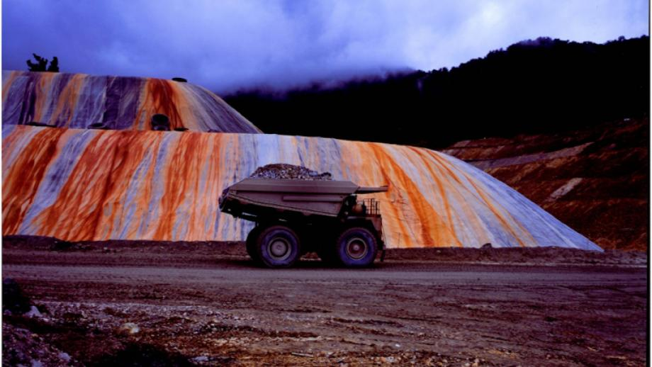 ANUA269/2 An ore truck drives past a plastic covered second-grade ore stockpile, c. 1997-2002, Lihir Island, PNG, Dr M Macintyre & Dr Simon Foale collection