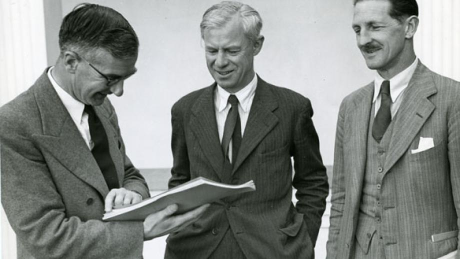 RG Osborne, ANU Registrar speaking with Sir Keith Hancock and Professor Raymond Firth during the Easter conference